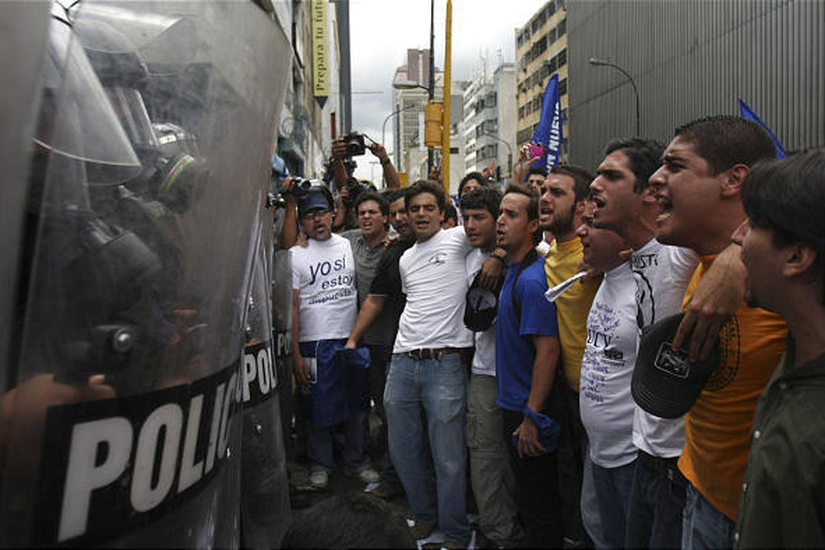 Opposition demonstrators shout slogans in front of police officers during a protest against an education bill in Caracas, Venezuela, Tuesday.