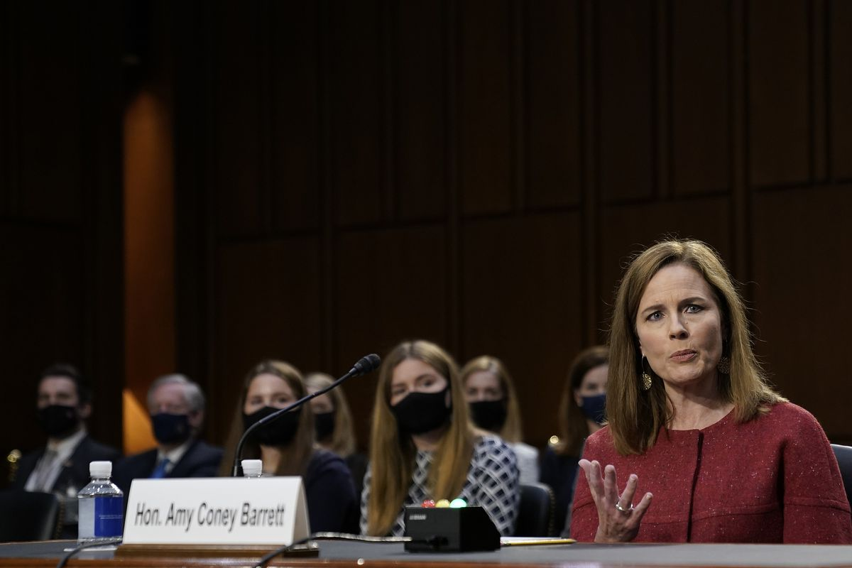 Amy Coney Barrett speaks in a hearing room with some of her children seated behind her.