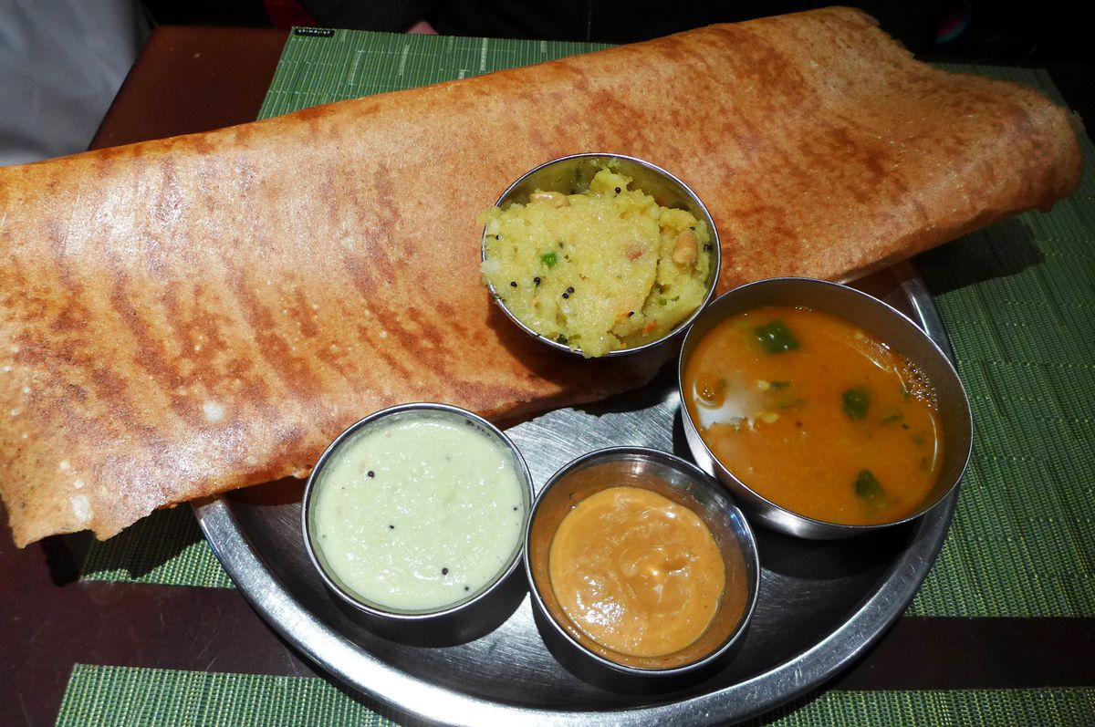 A giant rolled pancake with four small containers of potatoes and chutneys.