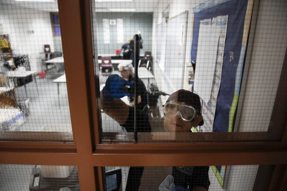 Jose Garcia cleans a window at Bruce Randolph School in Denver on Thursday, March 19, 2020.