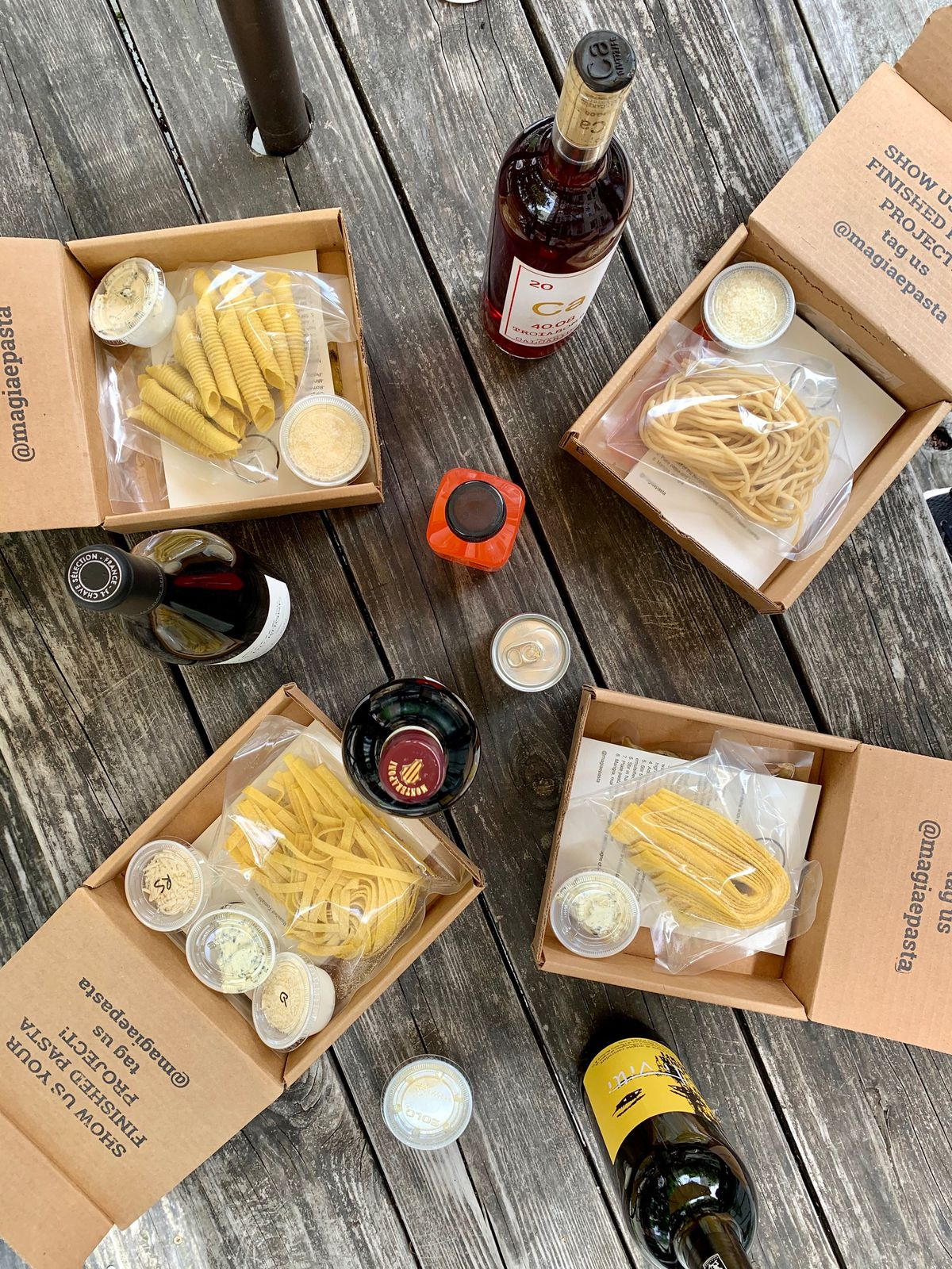 A wooden table with cardboard boxes open to reveal packaged dry pasta alongside bottles of wine