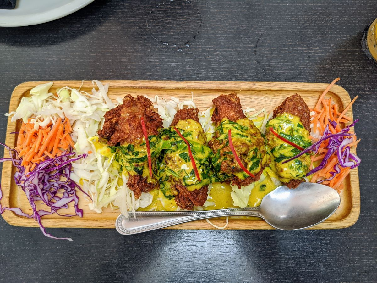 Phuket fried chicken wings at Emporium Thai on a wood plate with shredded vegetables.