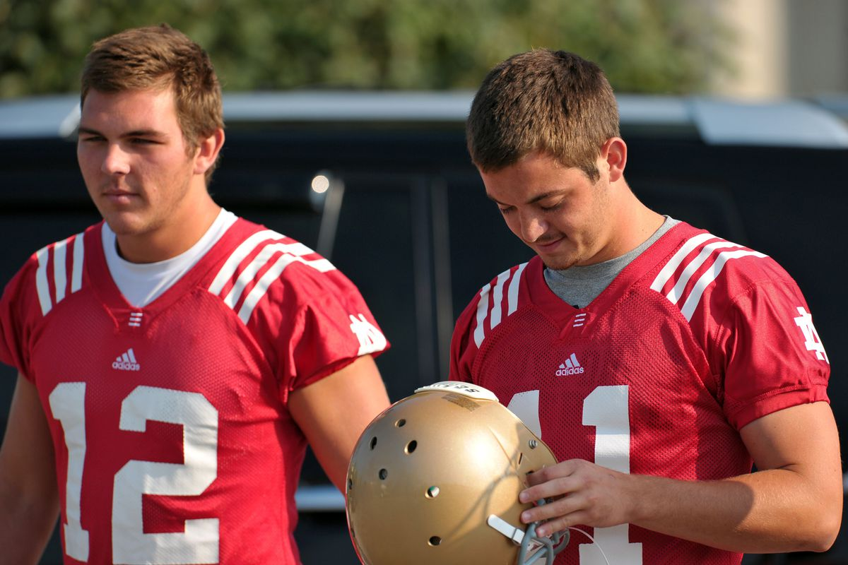 Aug. 4, 2012; South Bend, IN, USA; Notre Dame Fighting Irish quarterbacks Andrew Hendrix (12) and Tommy Rees (11) walk into practice at the LaBar Practice Complex. Mandatory Credit: Matt Cashore-US PRESSWIRE