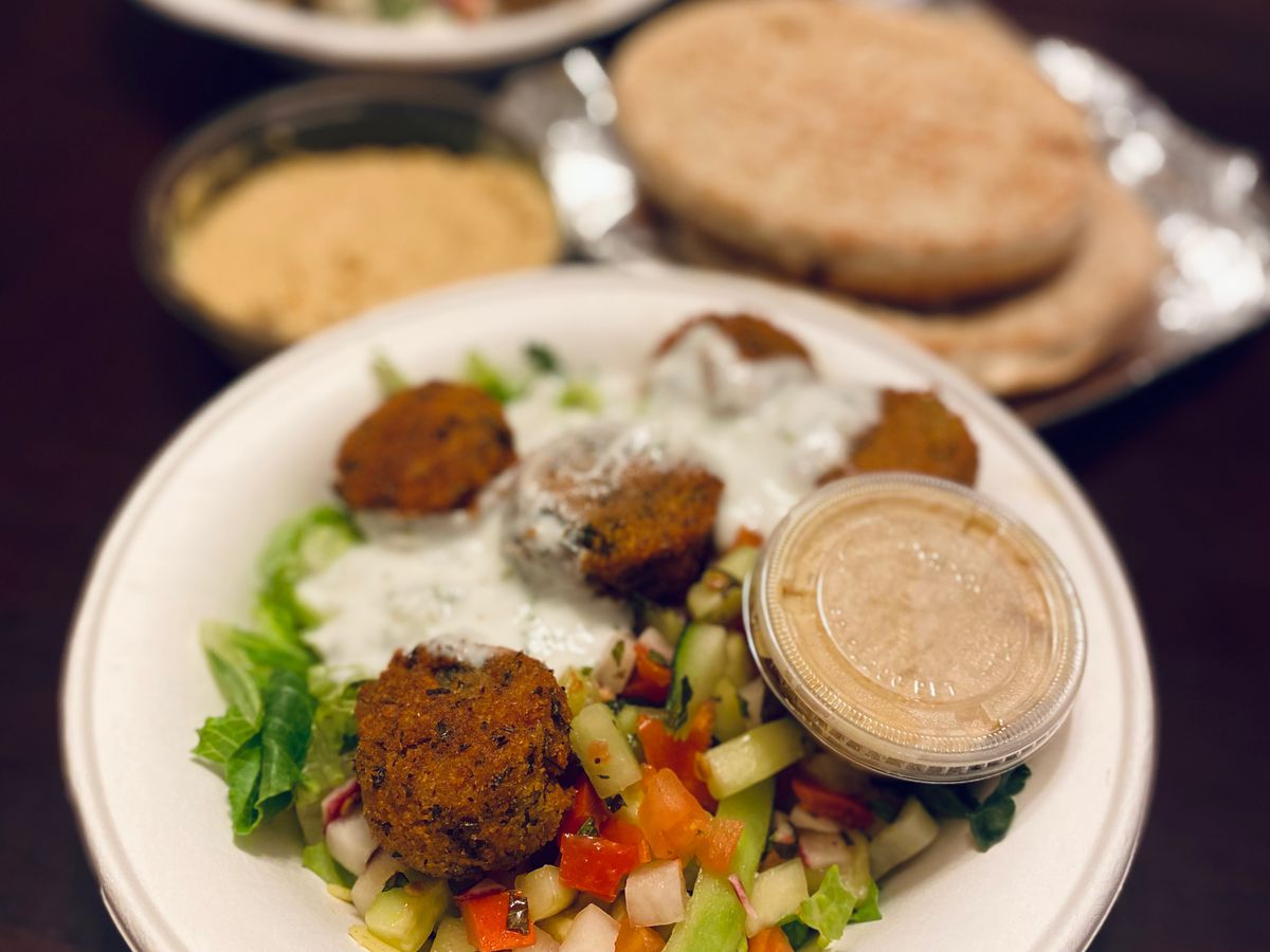 A bowl of Baba's hummus comes topped with falafel, a cucumber salad, and garlic sauce