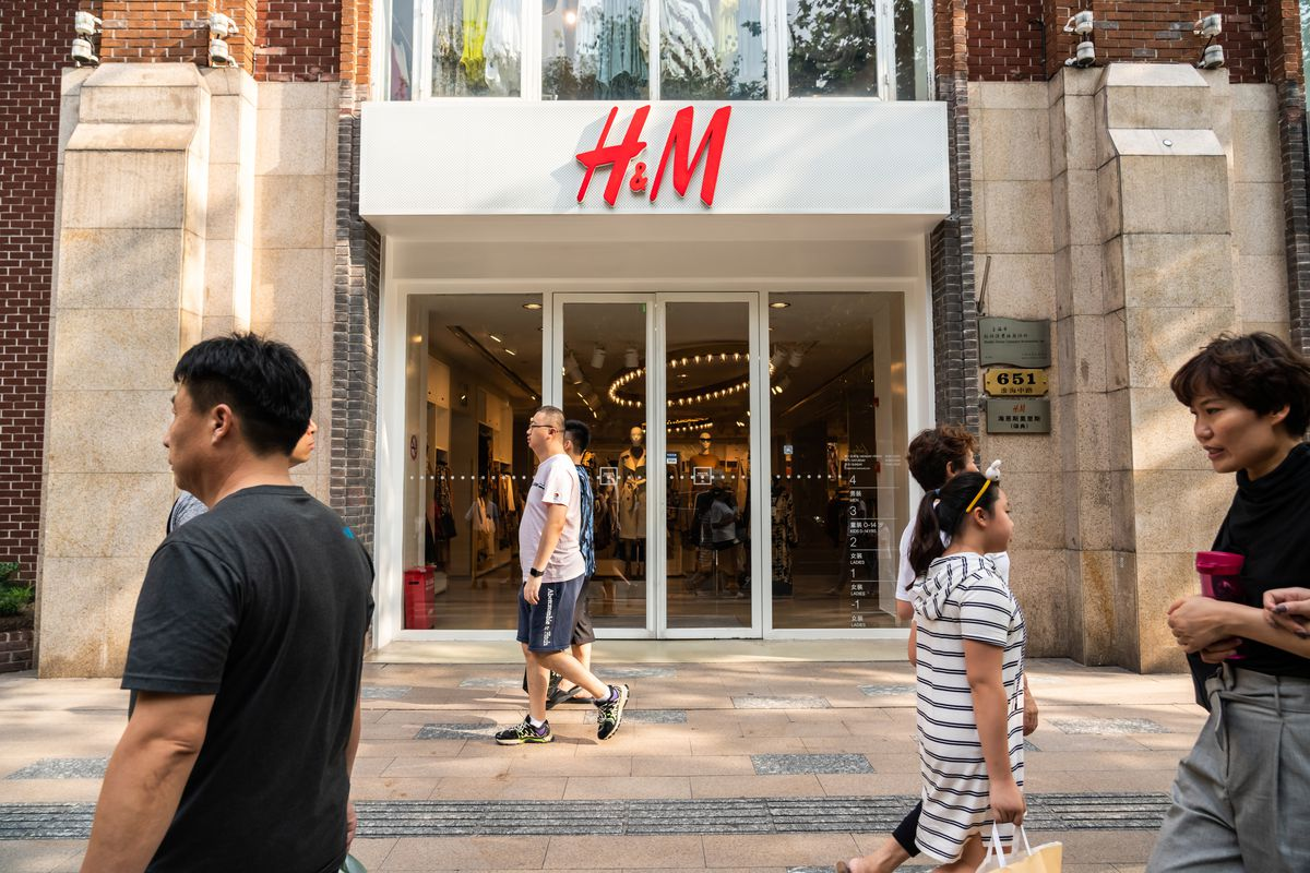 The exterior of an H&M story with pedestrians walking by.