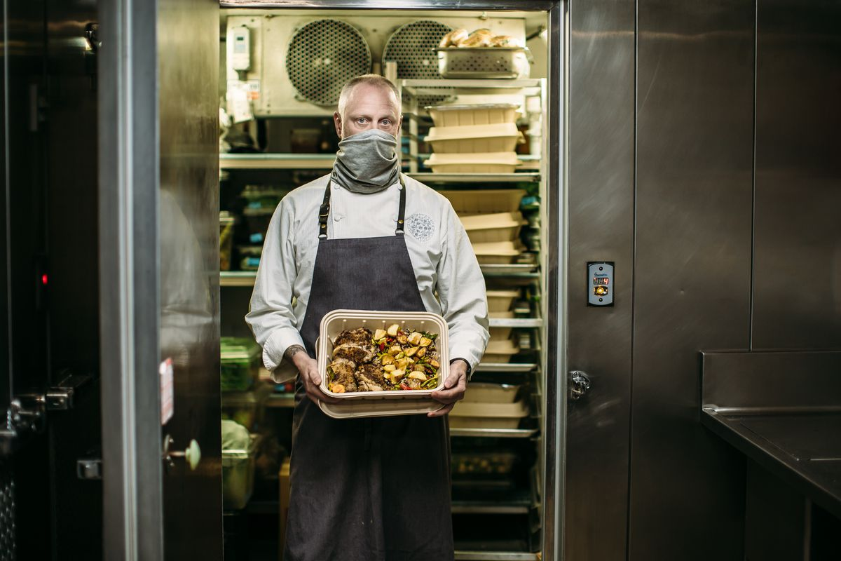Kyle Connaughton stands in the doorway of a kitchen walk-in, holding a compostable container of cooked chicken and vegetables. He wears a mask and an apron