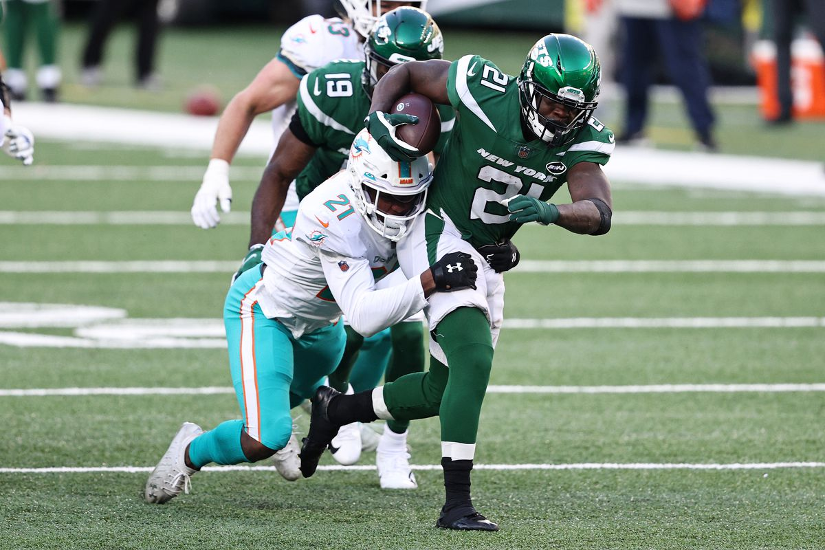 Frank Gore #21 of the New York Jets is tackled by Eric Rowe #21 of the Miami Dolphins during their NFL game at MetLife Stadium on November 29, 2020 in East Rutherford, New Jersey.