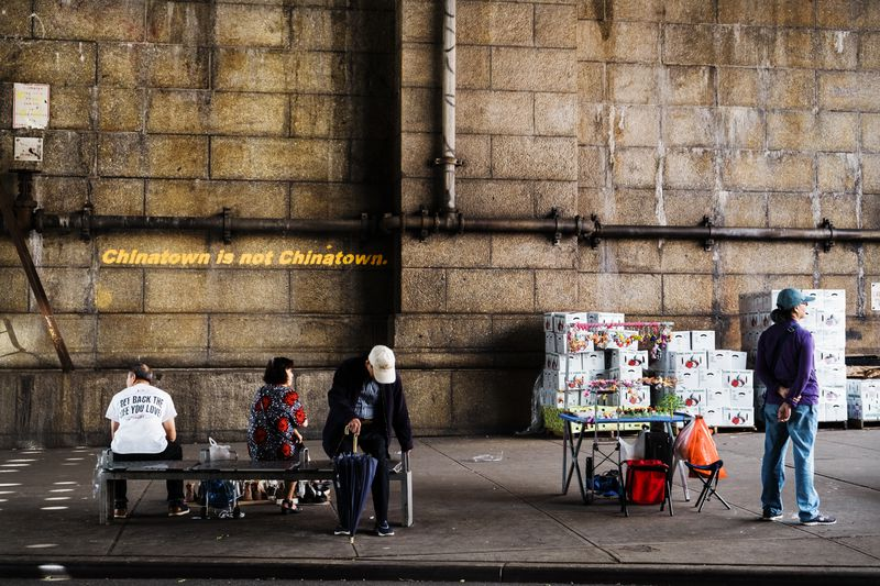 """People sitting on a bench beside a peddler under the Manhattan Bridge. Graffiti on the wall reads, """"Chinatown is not Chinatown."""""""