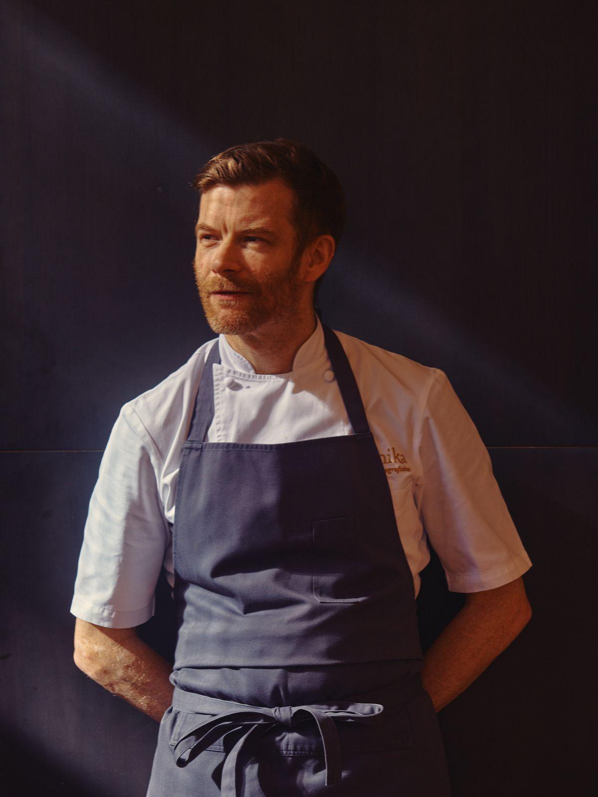 Robert Aikens wears an apron and a white shirt, against a black wall.