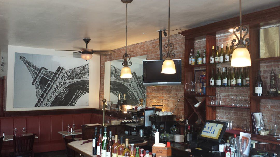 The bar at Le P'tit Paris Bistro, set in front of an exposed brick wall