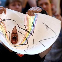 """A same-sex marriage supporter makes a megaphone out of his sign while booing at a """"Stand for Marriage"""" rally at the state Capitol in Salt Lake City on Tuesday, April 28, 2015."""