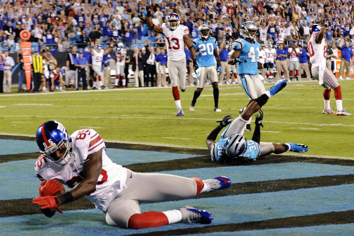 New York Giants wide receiver Martellus Bennett (85) catches a touchdown pass past Carolina Panthers safety Charles Godfrey (30) during the first quarter of an NFL football game in Charlotte, N.C., Thursday, Sept. 20, 2012.