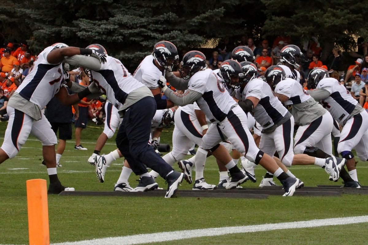 Denver Broncos offensive linemen participate in drills during the fourth day of training camp practice on Sunday, July 28, 2013.