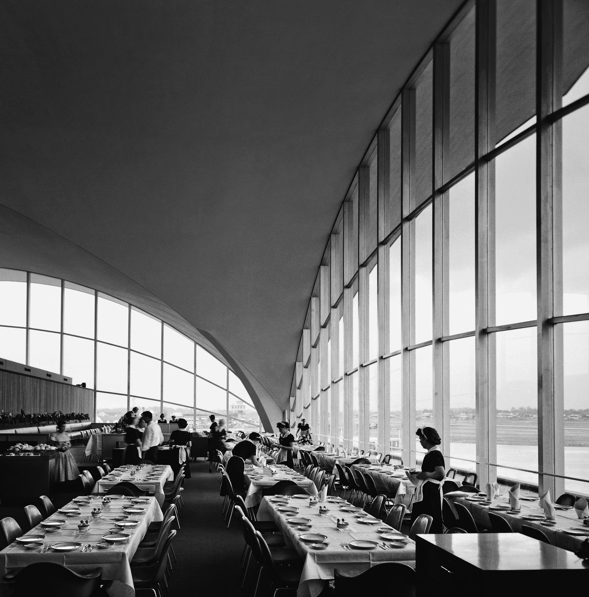 The inside of an airport terminal which features large windows and a curbed ceiling.