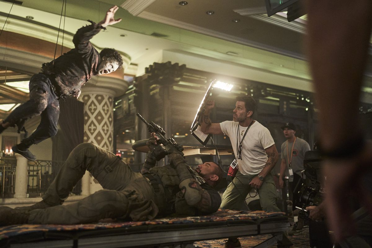 Dave Bautista lies on his back, pointing his gun up at a zombie actor suspended above him on wires, as director Zack Snyder holds a light reflector above him on the set of Army of the Dead
