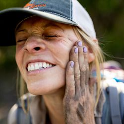 Hawkwatch International conservation biologist Jordan Herman wipes dirt off her face, with an even dirtier hand, after visiting a golden eagle nest in Tooele County on Thursday, June 17, 2021.
