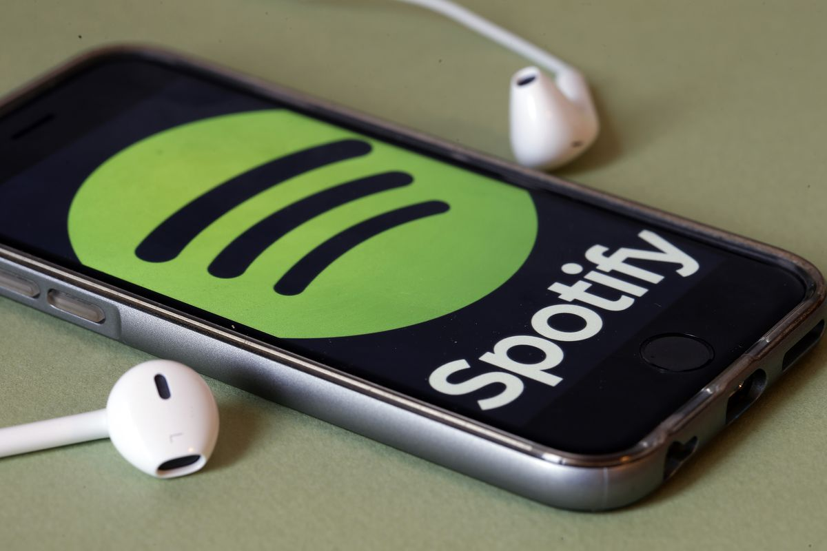 a mobile phone displaying the Spotify logo, plus headphones