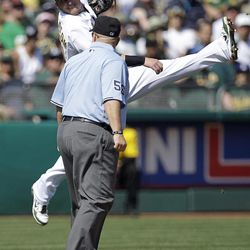 Oakland Athletics third baseman Josh Donaldson misses a throw allowing Seattle Mariners' John Jaso to score in the second inning of a baseball game Saturday, Sept. 29, 2012, in Oakland, Calif. At right is third base umpire Eric Cooper.