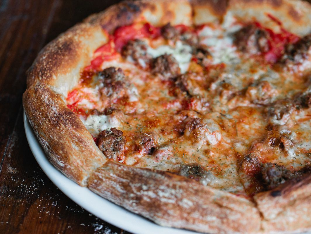 A golden crusted pizza with sausage and red sauce.