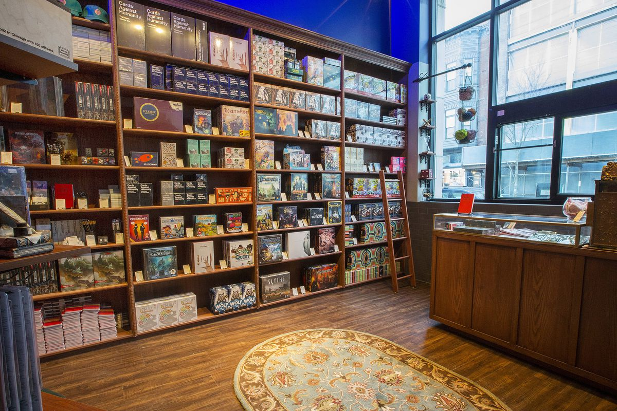 Inside the gift shop, a small ladder gives easy access to tall bookcases overflowing with multiple copies of hit boad games. Titles include the D&D Starter Set, Ticket To Ride, Scythe, and Scrabble.