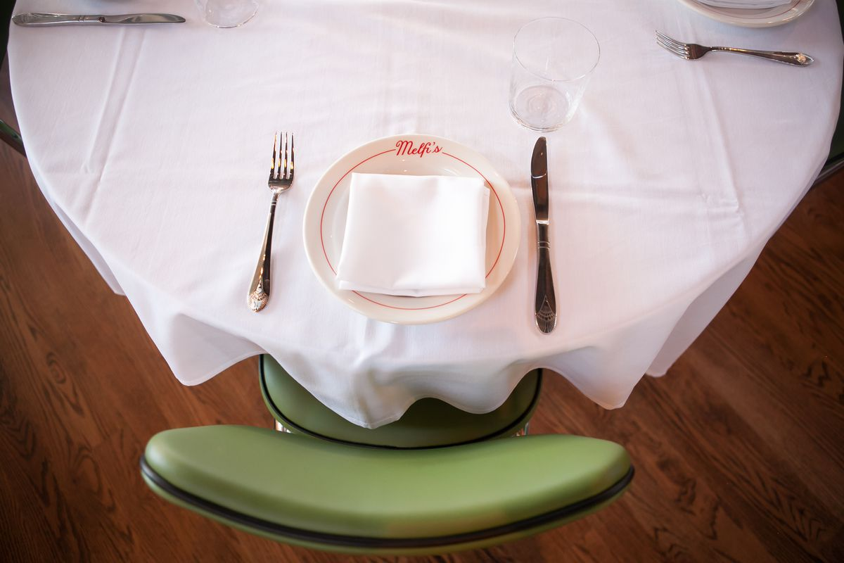 Photo of a table with a dish and green chair