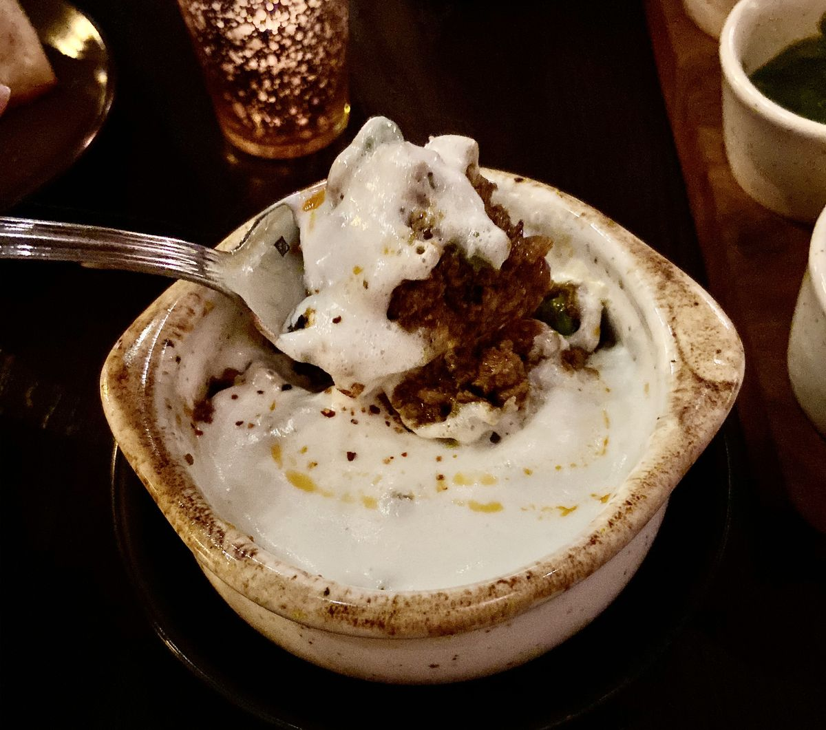 A spoon lifts ground spiced lamb from under a layer of potato mousse in a ceramic pot.