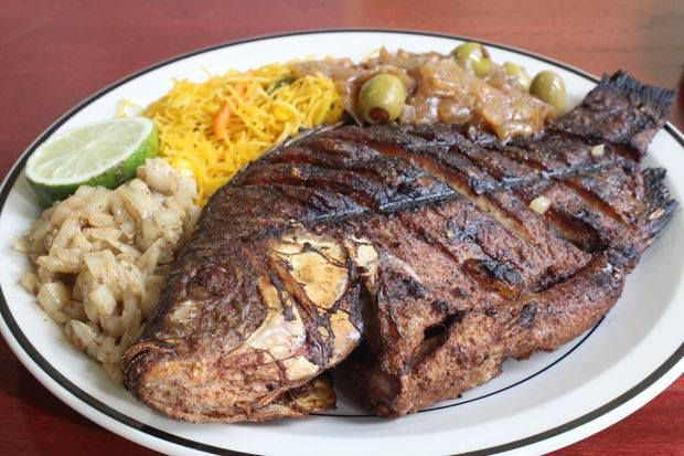 A plate of whole grilled fish, rice, and sides.