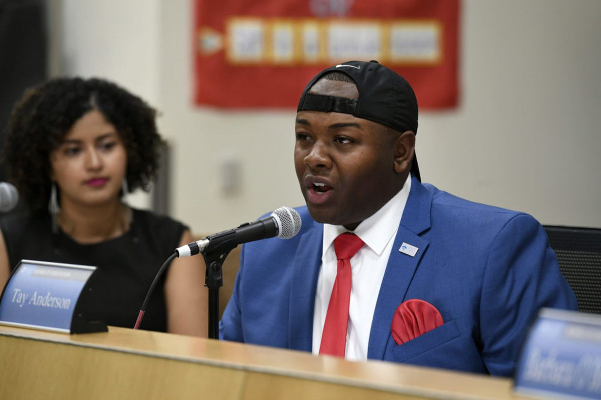 Tay Anderson, wearing a blue suit, red tie and handkerchief, and black baseball hat, speaks into a microphone from the dais of the Denver school board.