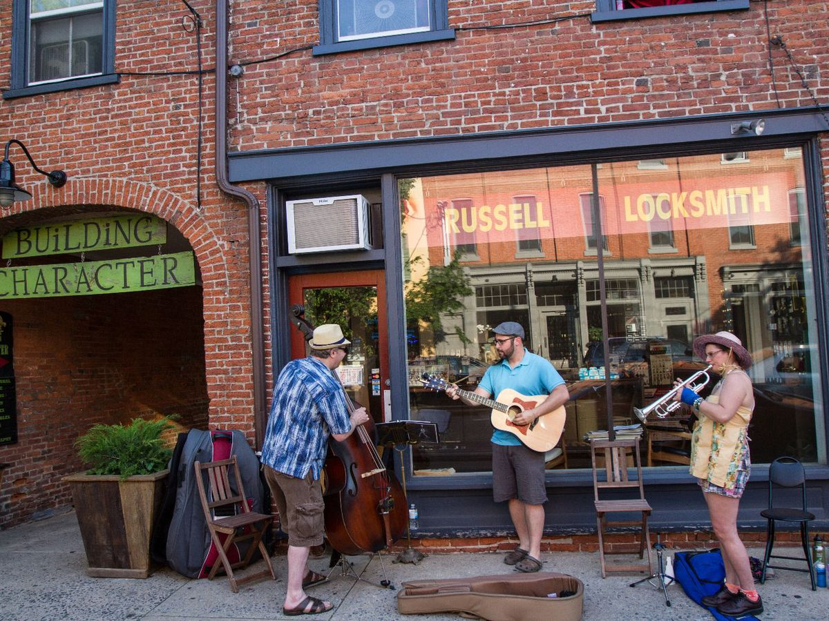 Street musicians stand and play on a sidewalk outside of a store on a street in Lancaster City, Pennsylvania.