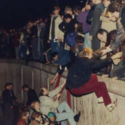 East Berliners get helping hands from West  Berliners as they climb the Berlin Wall which has divided the city since the end of World War II, near the Brandenburger Tor (Brandenburg Gate), early morning, Nov. 10, 1989. The citizens facing the West celebrate the opening of the order that was announced by the East German Communist government hours before.