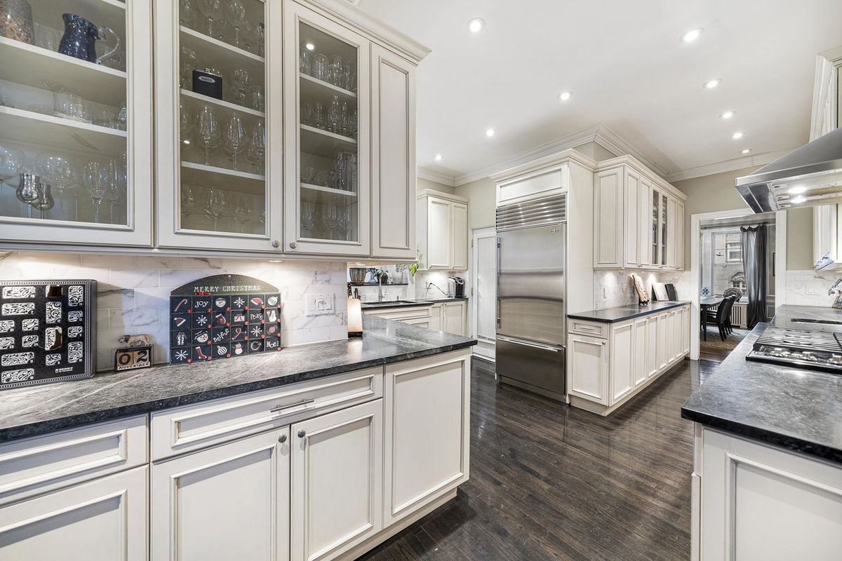 A view of the kitchen with white cabinets, long black countertops, and stainless steel appliances.