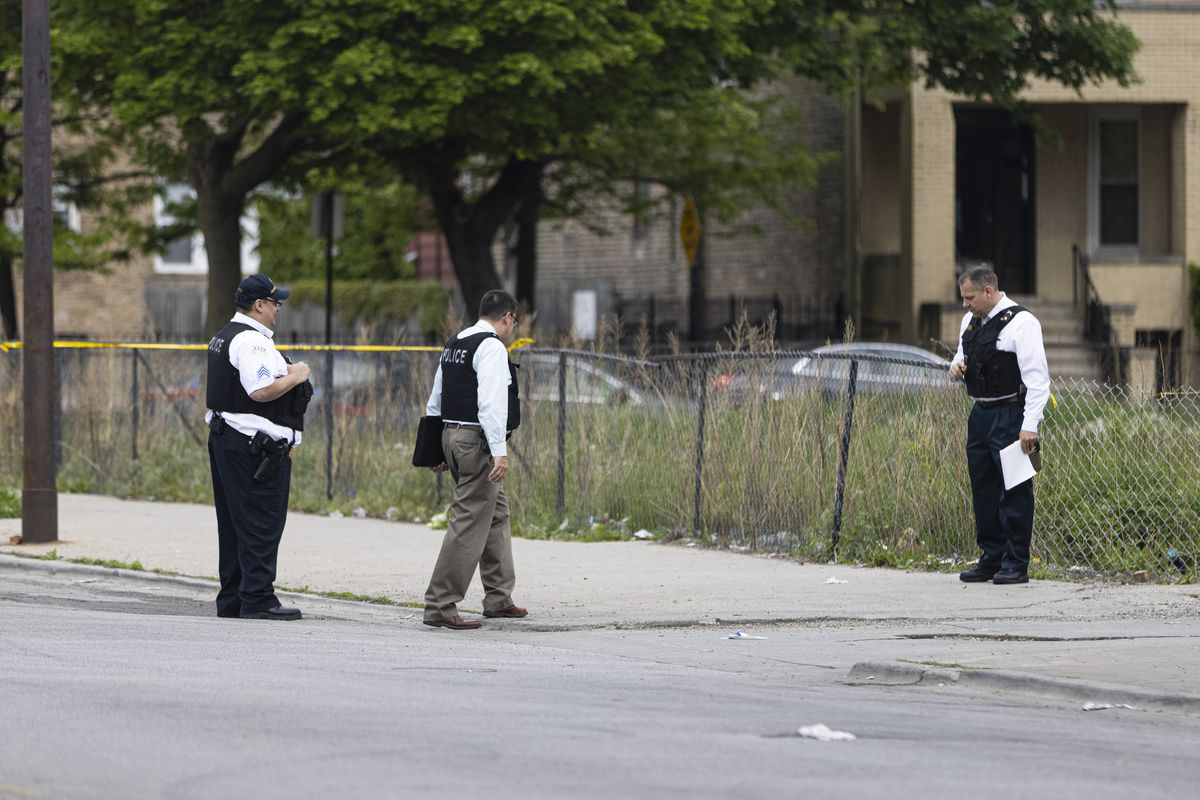 Police investigate the scene where a teenage girl was shot at 61st Street and South King Drive in Washington Park, Monday, May 17, 2021.