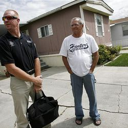 Shawn McNair, left, and Charles White talk Monday about neighbor Domingo Chavez-Lopez, who was shot to death Sunday.