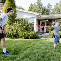 Peter Larsen plays with his brother George on the front lawn of their home in Millcreek on Wednesday, Sept. 16, 2020.