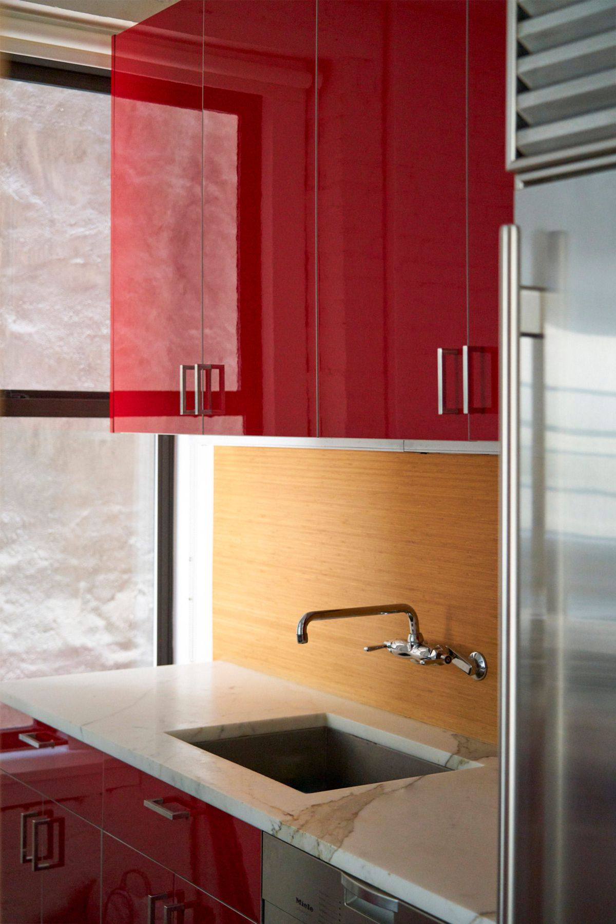 A close-up view of red kitchen cabinets, marble counters, and a stainless-steel fridge.