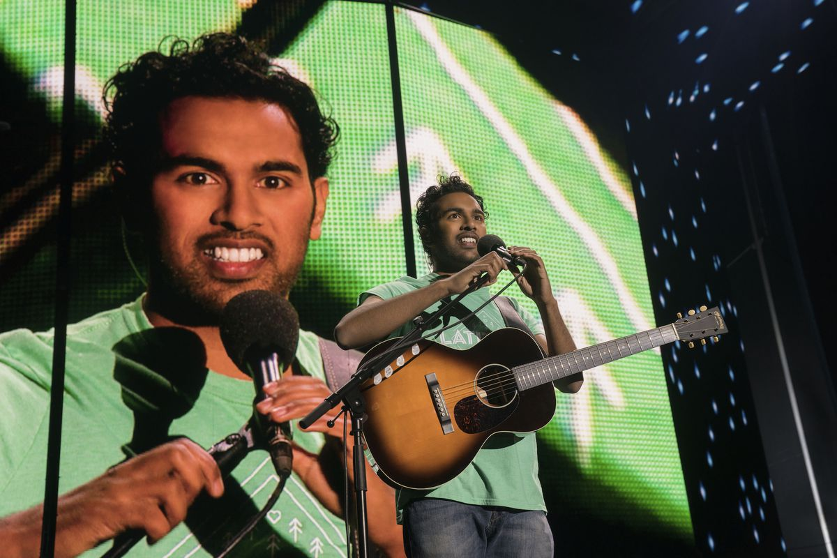 an Indian man holding a guitar adjusts his microphone on stage with a big screen of himself behind him