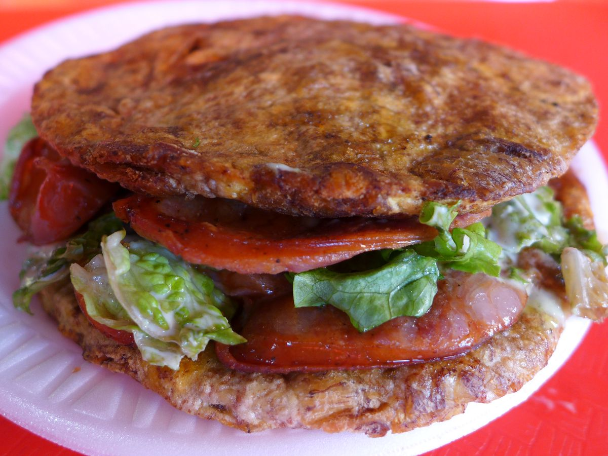 A plantains sandwich filled with sausage.