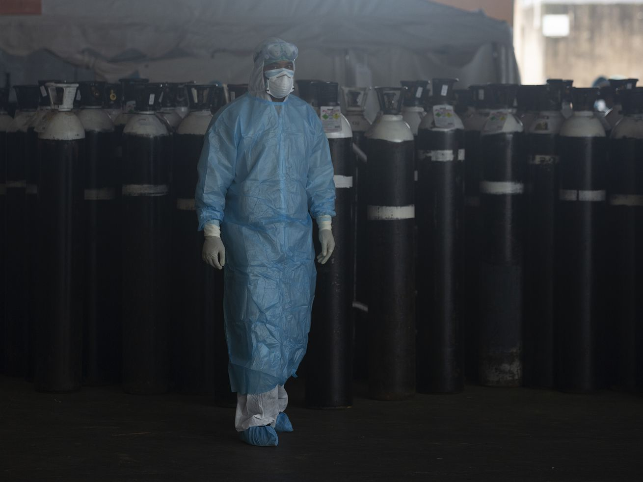 A front-line worker passes oxygen ciylinders at the Steve Biko Academic Hospital's outside parking area in Pretoria, South Africa, Monday, Jan. 11, 2021.