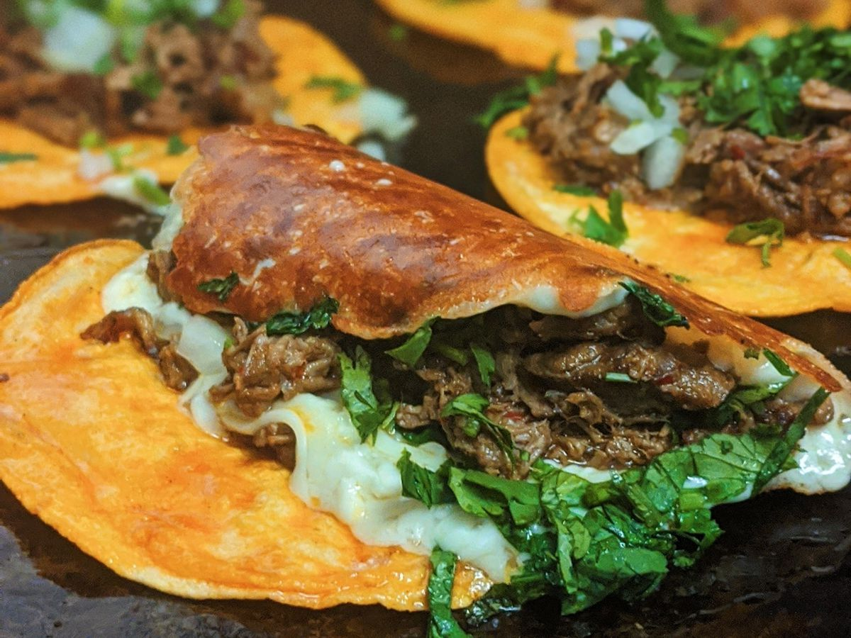 Tacos with meat, cheese, and cilantro on a black griddle