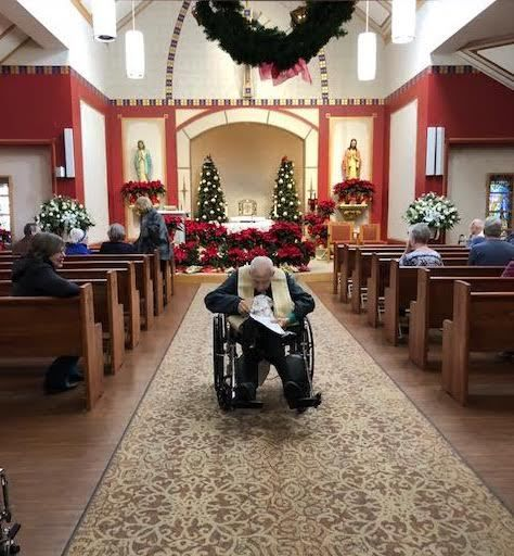 """Father George McKenna at the last mass he attended on Dec. 30, passing out bulletins from his """"God is Good!"""" blog. 