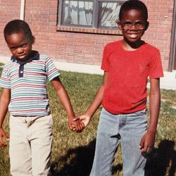 Tope Folarin, right, at age 6, with his brother, Ola, outside their apartment in Bountiful, Utah.
