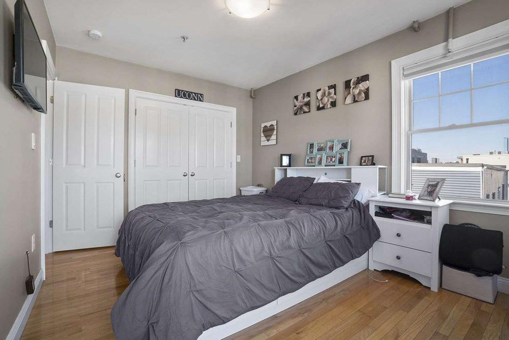 A bedroom with a bed next to a set of closed closet doors.