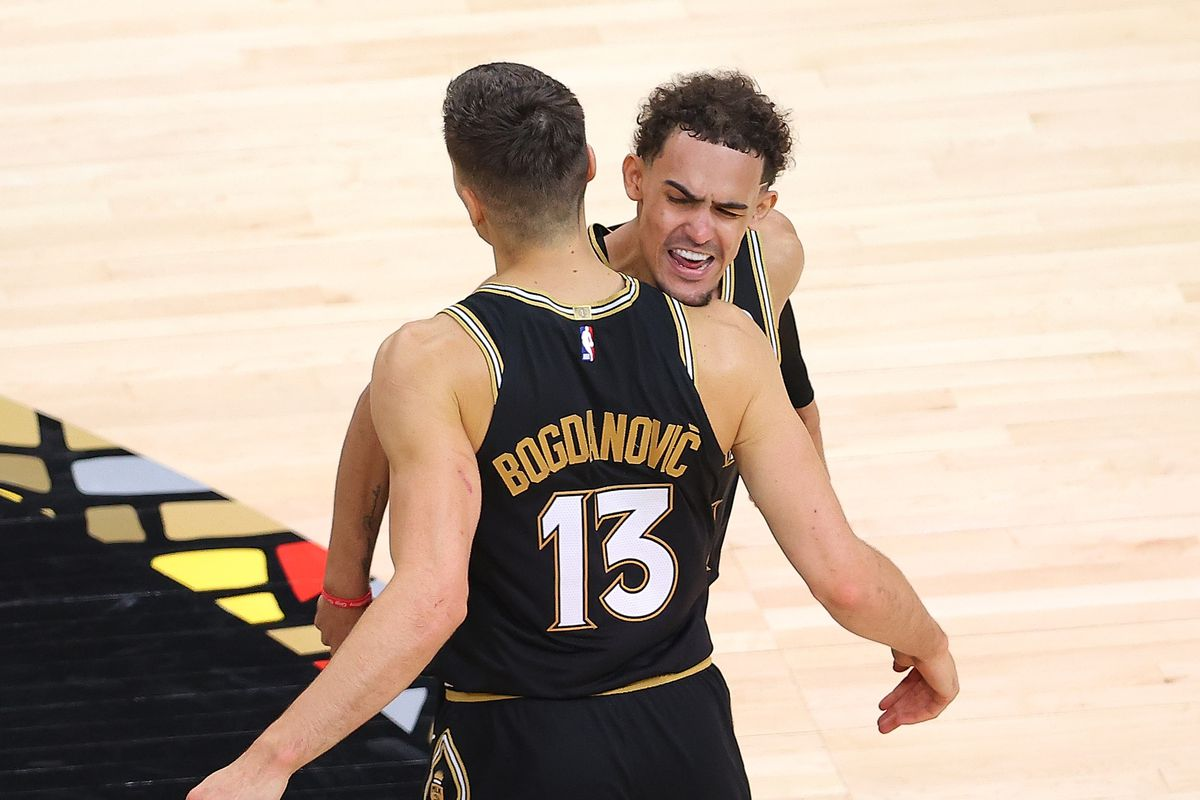Bogdan Bogdanovic of the Atlanta Hawks reacts with Trae Young after a three-point basket against the New York Knicks in the first half during game four of the Eastern Conference Quarterfinals at State Farm Arena on May 30, 2021 in Atlanta, Georgia.