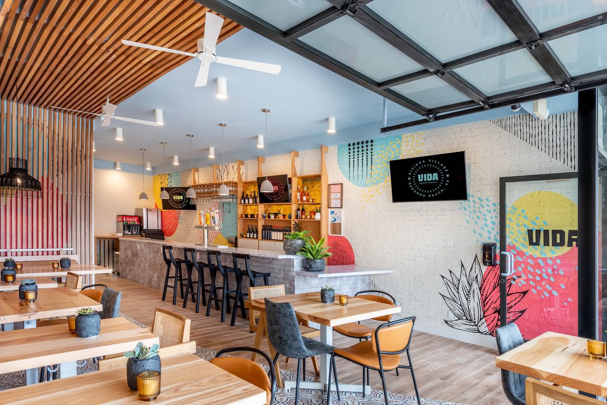 An angled look into a small casual restaurant with a bar in the back and painted brick wall with splashes of color.