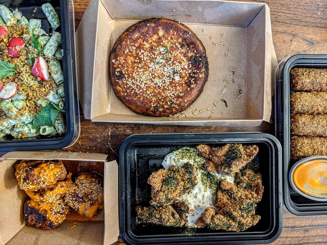 Overhead view of a takeout spread, including a round piece of cornbread, fried chicken, snap pea salad, and more.
