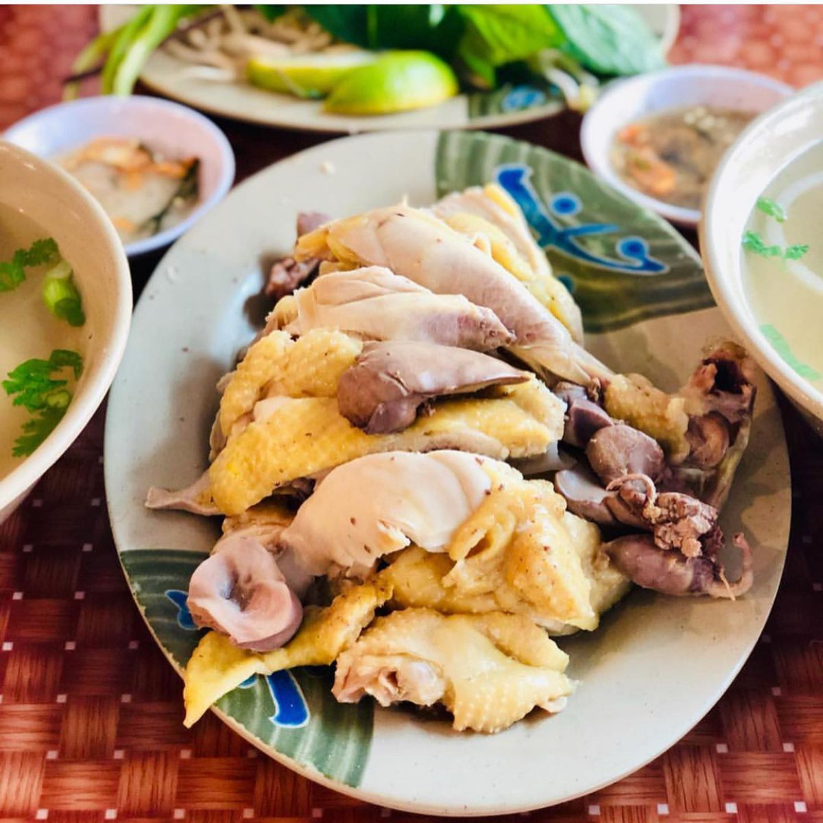 A pile of whole chicken parts and two bowls of pho and herbs