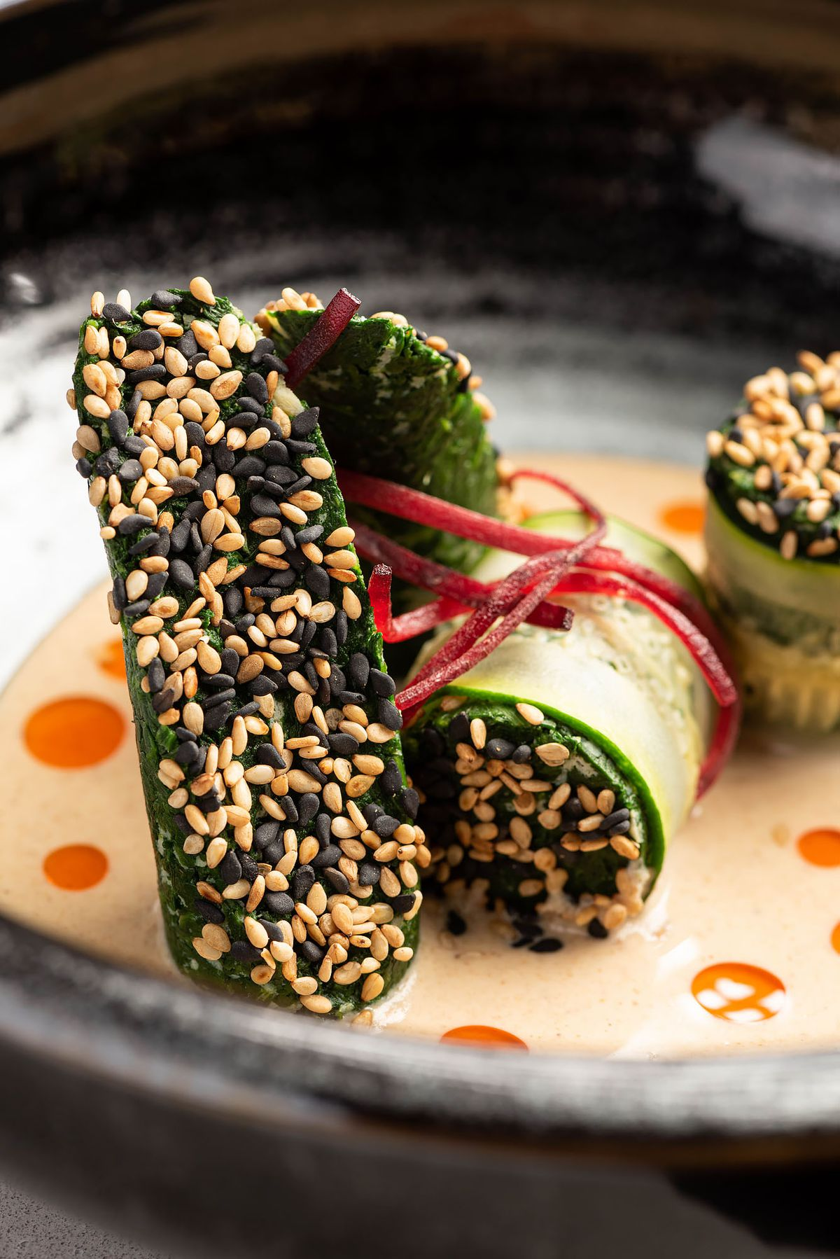 Compressed spinach salad with sesame seeds and sesame dressing.