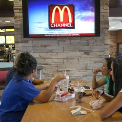 In this photo taken Friday, Sept. 7, 2012, McDonald's patrons watch the new McDonald's television channel at a McDonald's restaurant in Norwalk, Calif. McDonald's is testing its own TV channel in 700 California restaurants in a pilot project that could expand to all the company's restaurants.