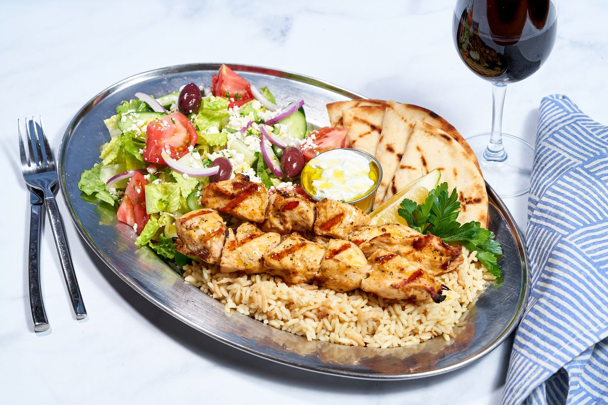 Skewers on a plate with rice and pita