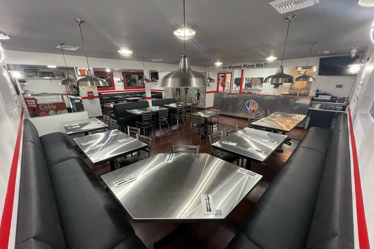 A dining room with stainless steel tables and dark gray seating
